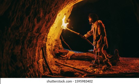 Primeval Caveman Wearing Animal Skin Exploring Cave At Night, Holding Torch with Fire Looking at Drawings on the Walls at Night. Cave Art with Petroglyphs, Rock Paintings. Side View