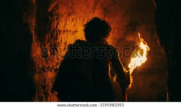 Primeval Caveman Wearing Animal Skin Exploring Cave At Night Holding Torch with Fire Looking at Drawings on the Walls at Night. Neanderthal Searching Safe Place to Spend the Night. Back View