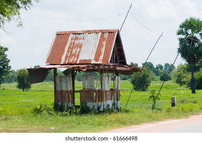 Primitive bus stop shelter in rural Nakhon Ratchasima, Thailand. Rice fields in the background.