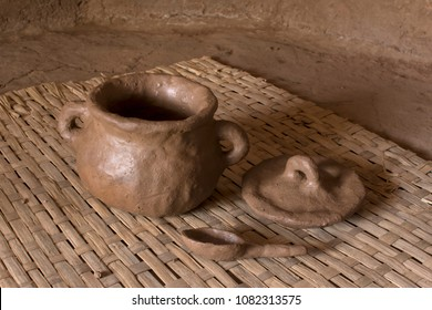 Primitive fresh thrown pottery consisting of bowl, lid and spoon sit drying on woven mat inside adobe hut with earthen floor