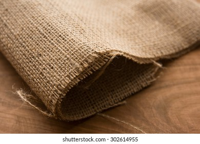 Primitive hemp cloth on rustic wooden table. Shallow depth of field.