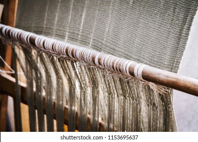 Primitive Loom or Vertical Loom in Weaving. Warp-weighted. Old hand loom during weaving of the fabric, medieval age. Reconstruction of a vertical neolithic loom with string heddles.
