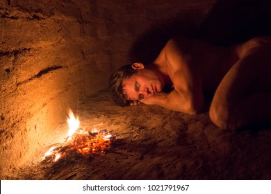 Primitive man lies naked sleeping on dirt floor of adobe hut next to campfire
