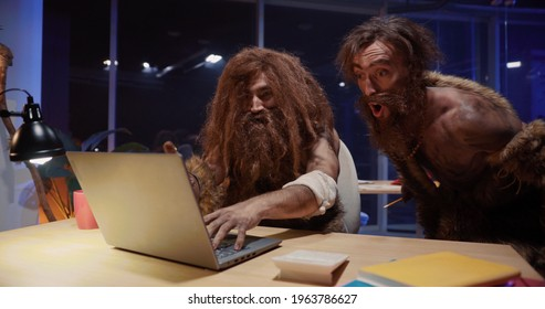 Primitive neanderthal people couple traveling through time working in contamporary office playing woith gagdets interacting new things.