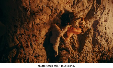 Primitive Prehistoric Neanderthal Wearing Animal Skin Draws Animals and Abstracts on the Walls at Night. Creating First Cave Art with Petroglyphs, Rock Paintings Illuminated by Fire. Back View