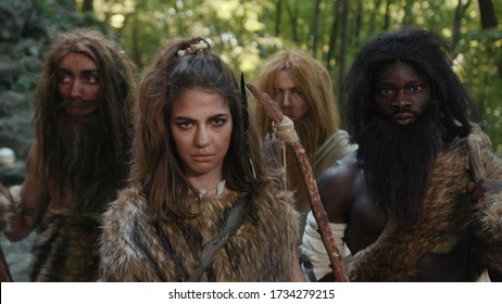 Primitive tribe with female archer leader looking aggressively at camera. Multi-ethnic prehistoric family. Stone-age period of matriarchy. Homo sapiens.