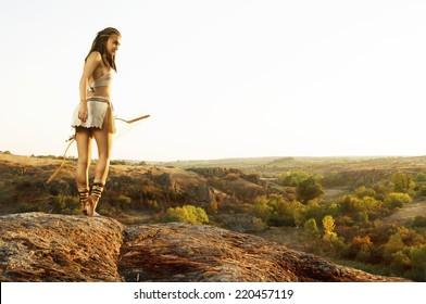 Primitive woman  holding a bow. Amazon woman