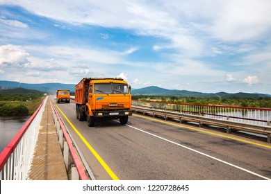 PRIMORYE, RUSSIA - June 6, 2018: Two dump trucks Kamaz moving over the bridge
