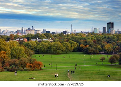 Primrose Hill at sunset, with the financial center in background, London, UK