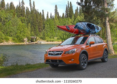 Prince George, BC / Canada - June 11 2018: Sporty orange crossover SUV with kayaks on roof rack parked beside whitewater river on beautiful sunny day.