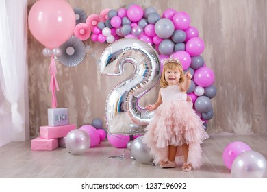 Princess baby girl celebrating life event wearing golden crown and pink airy dress. Cute girl posing in pastel colors studio shoot with air baloons and cake