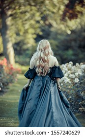 Princess with blond hair running away in blooming garden