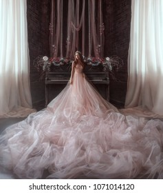 princess castle Gothic room background old piano. girl in luxurious lush full expensive pink dress very long skirt train. Creative wedding decoration flowers branches hanging fabric white curtains
