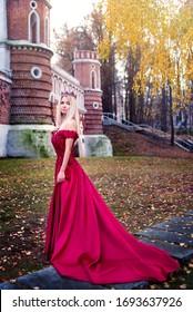 Prinzessin in Kronen und rotem Kleid auf Burghintergrund, Königin. Märchen