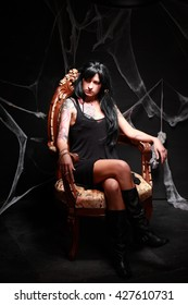 Princess of darkness. Studio shot of attractive young brunette girl with tattoo sitting on the throne surrounding by cobweb