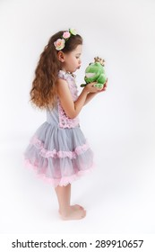 princess girl kissing a frog green toad like a story tale on white