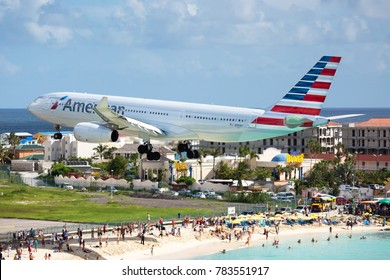 PRINCESS JULIANA AIRPORT, PHILIPSBURG / ST. MAARTEN (SAINT-MARTIN), ANTILLES - 08.15.2017. Passenger plane Airbus A330 of American Airlines flies extremely low over the Maho Beach and leisure tourists