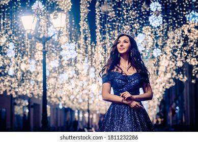 Prinzessin in langblauem Kleid steht nachts auf Bokeh-Hintergrund.