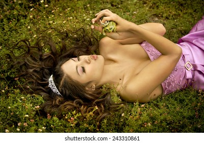 A princess lying in a bed of flowers, about to kiss her frog prince