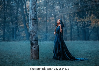 princess with red long hair dressed in blue expensive velvet royal cloak-dress, girl got lost in dark foggy forest, art photo, red-haired witch goes to totem monument in moonlight, pagan worship idol