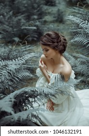The princess sits on the ground in the forest, among the fern and moss. On the lady is a white vintage dress with a deep cutout, beautifully emphasizes a chest. Art photo. Emotions of melancholy