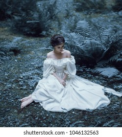 The princess sits on the ground in the forest, among the fern and moss. An unusual face. On the lady is a white vintage dress. Artistic photography. Emotions of melancholy and depression. Cold toning.