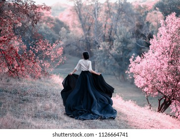 Princess in a vintage dress escapes. Walk through the picturesque autumn hills at sunset in pink tones. A long train of skirt fluttered on the run. Photo of a brunette girl with a back without a face.
