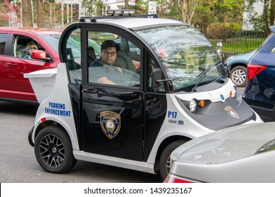 Princeton, New Jersey - April 28, 2019: A small electric smart car Gem made by Polaris is seen being used as a parking enforcement vehicle by a Princeton Police Officer on a street near parking meters