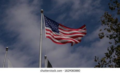 Princeton, New Jersey, USA, Oct. 7, 2020: US Flag fluttering in the wind against a blue sky with fluffy white clouds
