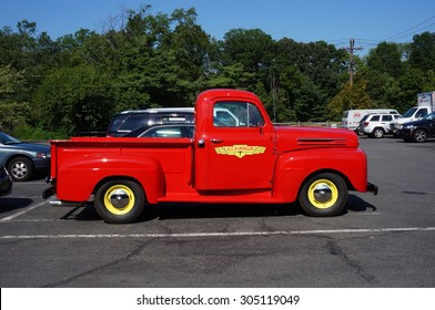 PRINCETON, NJ -7 JULY 2015- A vintage retro flaming red Ford pickup truck serving as an advertisement for the hardware chain stores Ace Hardware.
