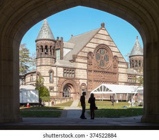 PRINCETON, NJ - October 20 2013: Autumn in one of the best and oldest universities in USA. Students standing under gate in Blair Arch with view at beautiful Alexander Hall.