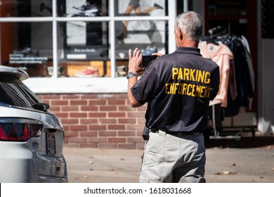 Princeton, NJ - October 4, 2019: Parking Enforcement man photographs license plate of car for evidence before issuing citation