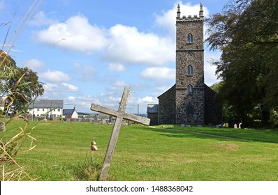Princetown England Autumn 2019. Church of St Michael and All Angels. Tower and side facade. Looking across neat grassed graveyard, crosses. Blue sky. Sign on wall detailing Church Conservation Trust.