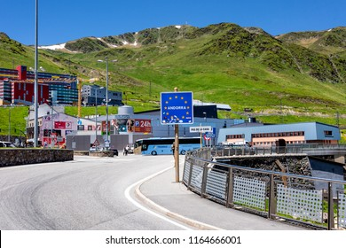 Principality of Andorra, El Pas de la Casa: European border sign at the French Andorran border in the famous Pyrenees with cityscape, green mountains and blue sky in the background. June 25, 2018