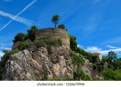 Principality of Monaco - 02.09.2018: Monaco-Ville with back side of Prince's Palace / Prince's Garden and historic city wall against blue sky