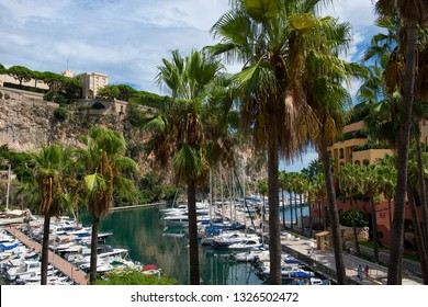 Principality of Monaco - 02.09.2018: View of Fontvieille harbor (Port de Fontvieille) and Monaco-Ville / Prince's Palace with palm trees in foreground