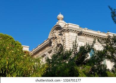 Principality of Monaco - 31.08.2018: Edge of Oceanographic Museum of Monaco seen through trees against blue sky