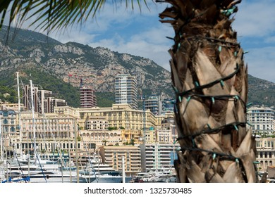 Principality of Monaco - 31.08.2018: panorama overview of Port Hercule and Monte-Carlo with palm tree in foreground