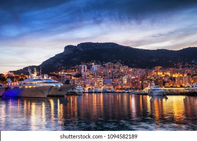Principality of Monaco picturesque evening skyline, city lights with reflection in Mediterranean Sea