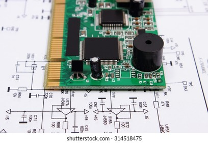 Printed circuit board with electrical components lying on construction drawing of electronics, drawings for engineer jobs, technology
