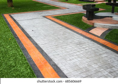 Printed concrete walkway with artificial grass texture background.