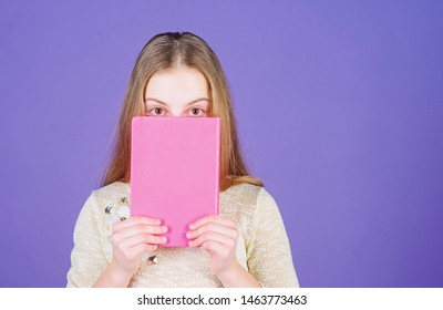 Printed literature. Adorable little child covering face with book of childrens literature. Cute small girl reading book in English literature. Literature for supplementary reading, copy space.