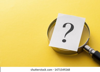 Printed question mark covering the lens of a magnifying glass over a yellow background with copy space in a conceptual image viewed close up from above