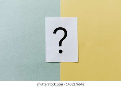 Printed question mark on white card on divided yellow and grey background placed in the center with lateral copy space in a conceptual image