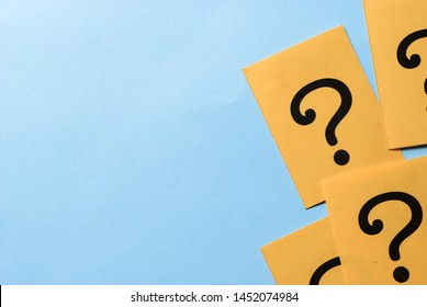 Printed question marks on yellow paper or card forming a right side border over a blue background with copy space