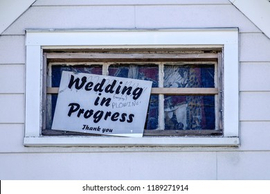 "Printed sign in window of house in a Midwestern college town: ""Wedding in Progress. Thank you."" With two handwritten words, ""banging"" and ""plowing."" For themes of courtship, privacy, youth."