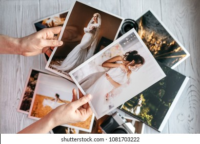 Printed wedding photos with the bride and groom, a vintage black camera and woman hands with two photos