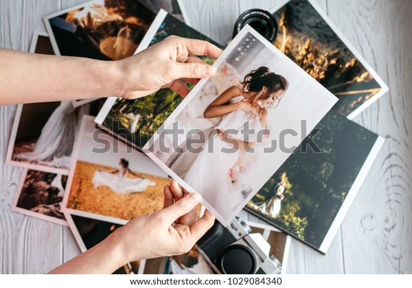 新郎新婦と結婚式の写真を印刷、ビンテージの黒いカメラと女性の手と写真