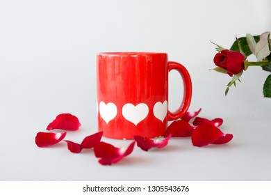 Printed white hearts on red coffee cup and rose isolated on white background