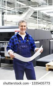 Printer. The man checks the print quality.